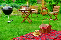 Picnic Blanket With Hat And Basket. Party Or Picnic Concept. Closeup Of Red Picnic Blanket With Straw Hat And Basket Or Hamper. Blurred Outdoor Wooden Furniture Stock Photography