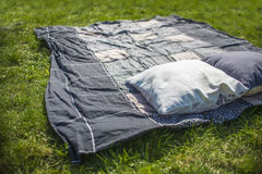 Picnic blanket with pillow on the grass Royalty Free Stock Photo