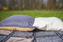 Picnic blanket with pillow on the grass Stock Photos