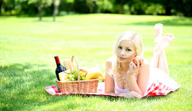 Picnic. Blonde young woman with basket Royalty Free Stock Image