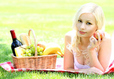 Picnic. Blonde young woman with basket of food royalty free stock images