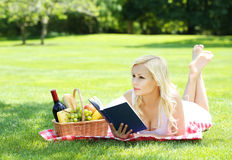 Picnic. Blonde young woman with book and basket Royalty Free Stock Photos