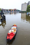 Picnic boat floating through a city Stock Image