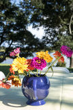 Picnic bouquet. A blue tea pot filled with colorful zinnias makes the perfect arrangement for a picnic table Stock Image