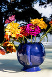 Picnic bouquet Closeup. A blue tea pot filled with colorful zinnias makes the perfect arrangement for a picnic table Royalty Free Stock Photography