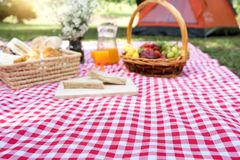 Picnic bread crossiant basket with fruit on  red white cloth. Blur picnic bread croissant basket with fruit on  red white cloth and vase flower with jar of Royalty Free Stock Photography