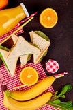 Picnic. Summer Time Rest. Picnic on brown table. Red checked tablecloth, basket, healthy food sandwich and fruit, orange juice.  Summer Time Rest. Flat lay Stock Image