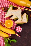 Picnic. Summer Time Rest. Picnic on brown table. Red checked tablecloth, basket, healthy food sandwich and fruit, orange juice.  Summer Time Rest. Flat lay Royalty Free Stock Photo
