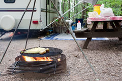 Picnic at the Campground. Corn and potatoes on an outdoor grill at a public park with a picnic table and camping trailer in the background Stock Photography