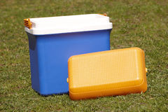 Picnic cooler in the grass in blue and orange tone Stock Image