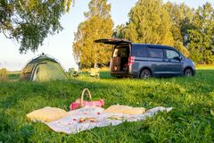 Picnic date in forest, tent and camp chairs, gray minibus with open door, blanket, wicker basket, wine glasses, snacks, fruit,. Picnic in the forest, tent and royalty free stock photo