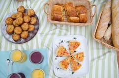 Picnic del buffet della prima colazione con pane, pasticcerie e la quiche Immagine Stock