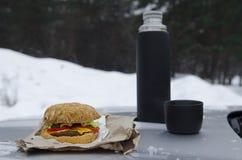 Picnic di inverno con tè e l'hamburger sul cappuccio di un'automobile d'argento contro lo sfondo della foresta fotografia stock libera da diritti