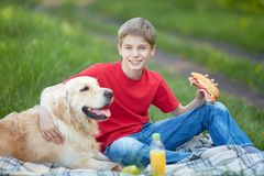 Picnic with dog. Portrait of cute lad and his fluffy friend having picnic Stock Images