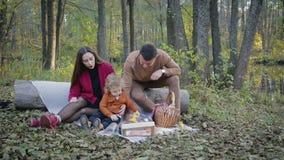 Picnic felice della famiglia dal lago archivi video