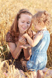 Picnic in field. Woman with child on picnic in field of wheat Royalty Free Stock Photo