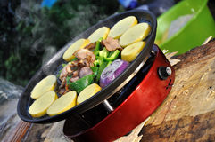 Picnic food. Making picnic food by portable cooker, shown as holiday, outdoor or travel Royalty Free Stock Photo