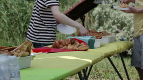 Picnic food distribution. On small table people take cakes stock video