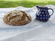Picnic  with freshly baked homemade bread with the milk jug. Picnic: Fresh homemade round loaf of bread with the ceramic milk jug, blue with white-brown dots Stock Images