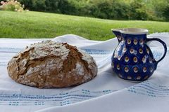 Picnic  with freshly baked homemade bread with the milk jug  2. Picnic: Fresh homemade round loaf of bread with the ceramic milk jug, blue with white-brown dots Stock Photos