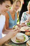 Picnic fun. Group of three friends having an outdoors picnic in the summer garden Stock Photo