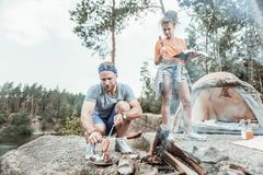 Bearded blonde-haired man broiling some sausages for picnic with girlfriend. Picnic with girlfriend. Bearded blonde-haired men wearing blue head band broiling stock photo