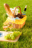Picnic on the grass. Glasses of white wine with fruits and picnic basket Stock Photo
