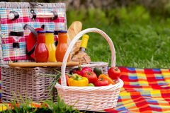 Picnic on the grass. Picnic basket with vegetables and bread. A Royalty Free Stock Photos