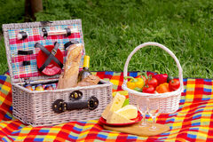 Picnic on the grass. Picnic basket with vegetables and bread. A Royalty Free Stock Photography