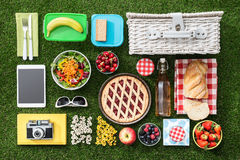 Picnic on the grass. Summertime picnic on the grass with basket, salad, fruit and accessories, flat lay Royalty Free Stock Photo