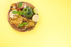 Picnic with grilled food. pineapple, peaches and corn on a barbecue. Delicious summer lunch and plastic dishes. Top view. royalty free stock image