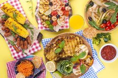 Picnic with grilled food. Sausages and corn on barbecue, shrimp, vegetables and fruits. Delicious summer lunch and plastic dishes. Top view stock image
