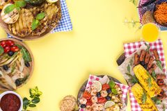 Picnic with grilled food. Sausages and corn on barbecue, shrimp, vegetables and fruits. Delicious summer lunch and plastic dishes. Top view royalty free stock photos