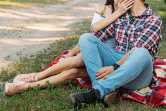 Picnic. a guy and a girl are sitting on a plaid veil on the grass, hugging and kissing. a man in a plaid shirt and jeans, with a w. A guy and a girl are sitting stock photos