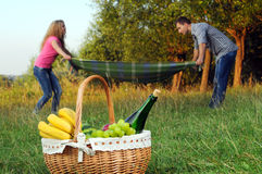 Picnic. Happy couple with a romantic picnic blanket lay on the background of a basket of fruit and wine Royalty Free Stock Photos