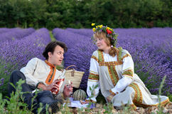 Picnic. Happy young couple having a picnic in a lavender field at evening time. Young men and beautiful girl in traditional russian clothes Stock Images