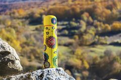 Picnic in the high autumn mountain with yellow thermos Stock Photography