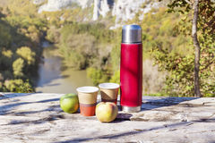 Picnic in the high mountain with red thermos,coffee and apples Royalty Free Stock Image