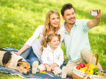 Picnic. Image of happy young family having picnic outdoors and making selfie Royalty Free Stock Image