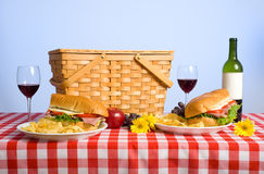 Picnic Lunch. A picnic lunch on a red and white gingham tablecloth including a sandwich, chip, grapes wine and a picnic basket in front of a blue sky background Stock Photo