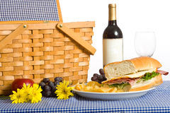Picnic Lunch. A picnic lunch consisting of a sandwich, potato chips and grapes on a Blue gingham or checked tablecloth Stock Image