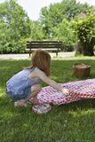 Picnic Lunch. Smally red-haired girl spreading a tablecloth on the grass for a picnic. Shallower depth of field - f/5 stock images