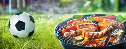 Grilled sausage on the flaming grill and soccer ball. Picnic on a meadow with bratwurst on flaming grill and a soccer ball Stock Images