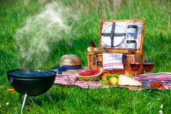 Picnic on a meadow. Picnic setting with red wine glasses, picnic hamper basket and burning fire in a portable barbecue Royalty Free Stock Photo
