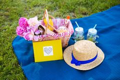 Picnic on nature. Beautiful flowers in a basket and yellow album lie on the grass-bright picnic Royalty Free Stock Photography