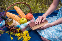 Picnic in nature at summer, basket with food. Young woman with a Royalty Free Stock Images