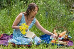 Picnic in nature at summer. Young woman in romantic blue dress i Stock Photography