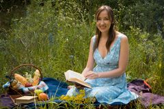Picnic in nature at summer. Young woman in romantic blue dress i Stock Images