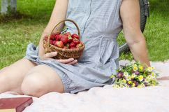 On a picnic  a woman sits on a plaid on the grass and holds a basket with red ripe strawberries and a bouquet of wild flowers. royalty free stock image