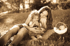 Picnic in park. Woman and child having picnic in park - monochrome photo in retro style, sepia toned Royalty Free Stock Image